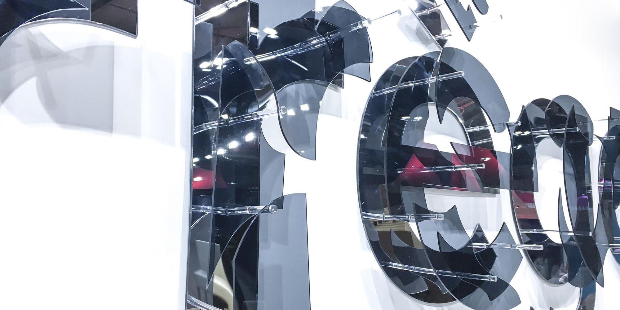 décomposition Courrèges en pièces de plexiglas noir translucide et miroir inspirées du motif de la collection lunettes 2017 de la marque: réalisation d'une enseigne de 4 mètres de long destinée à orner le stand de la marque sur le Mido Eyewear Show à Milan